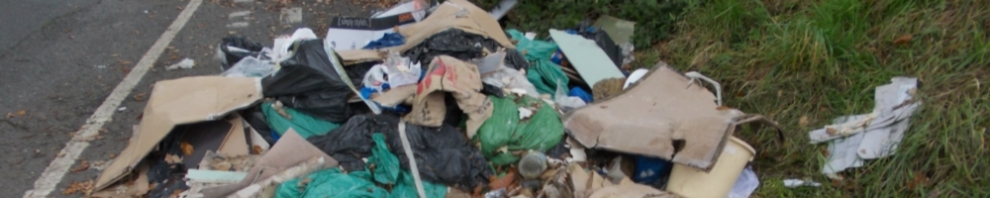 Fly tipping rubbish dumped by the side of a road
